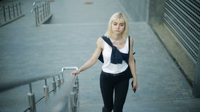 Young blonde woman climbs the stairs in the city. Moves towards the camera and passes by. stock video footage