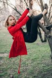 Young blonde woman climbs on tree in spring garden on background of blossoming trees. Stock Image