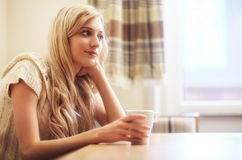 Young blonde woman with coffee cup at the table Stock Photography