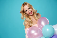Young blonde woman with colored balloons Royalty Free Stock Image