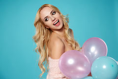 Young blonde woman with colored balloons Royalty Free Stock Photo