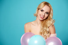 Young blonde woman with colored balloons Stock Photos