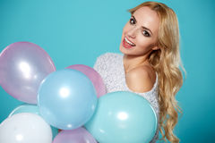 Young blonde woman with colored balloons Stock Photography