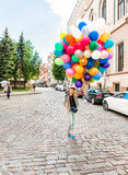 Young blonde woman with colorful latex balloons. Royalty Free Stock Photo