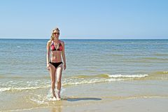 Young blonde woman coming out of the water Stock Images