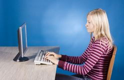 Young blonde woman at the computer royalty free stock image