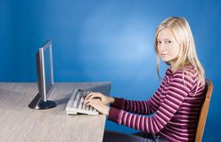 Young blonde woman at the computer Royalty Free Stock Images