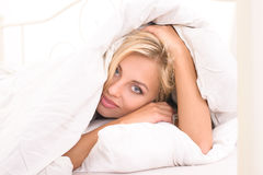Young blonde woman covered with blanket Royalty Free Stock Image