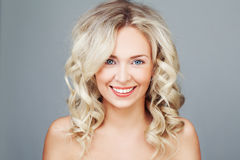 Young Blonde Woman with Curly Hair Smiling Stock Images