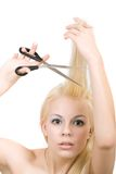 Young blonde woman cuts off his hair Stock Photos