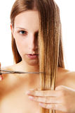 Young blonde woman cutting her hair with scissors. Royalty Free Stock Photos