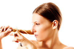 Young blonde woman cutting her hair with scissors. Royalty Free Stock Photography
