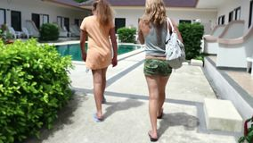Young blonde woman with daughter walking along an avenue under palm trees to the pool stock video