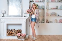 Young blonde woman decorating room with beautiful flowers. Beautiful woman arranging flowers and decorating her living stock photo