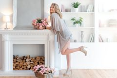 Young Blonde Woman Decorating Room With Beautiful Flowers. Beautiful Woman Arranging Flowers And Decorating Her Living Royalty Free Stock Image
