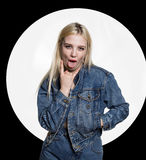 Young blonde woman in denim jaket and jeans shows tongue between two fingers on white background. indecent lifestyle. Young woman in denim jaket and jeans shows Royalty Free Stock Photography