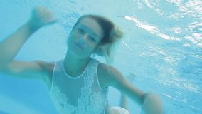 Young blonde woman does an underwater somersault and smiles happily stock video