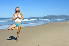 Young blonde woman doing exercises. At the beach along the atlantic ocean in Portugal Royalty Free Stock Photo