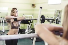Young blonde woman doing exercises with barbbell in a GYM. Strong woman, healthy lifestyle, losing weith concept Stock Photography