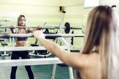 Young blonde woman doing exercises with barbbell in a GYM. Strong woman, healthy lifestyle, losing weith concept Royalty Free Stock Images