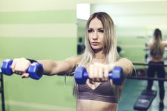 Young blonde woman doing exercises with dumbbells in a GYM. Healthy lifestyle concept Royalty Free Stock Images