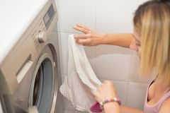 Young blonde woman doing laundry, shallow deep of field. Young blonde woman doing laundry, shallow deep of field stock images