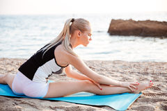 Young blonde woman doing stretching exercises on yoga mat. Portrait of a young blonde woman doing stretching exercises on yoga mat outdoors in the morning Royalty Free Stock Images