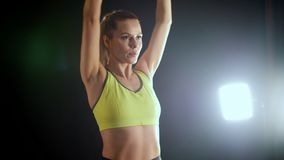 Young blonde woman doing training with dumbbells in hands - attractive fitness model in studio. Slow-motion stock video