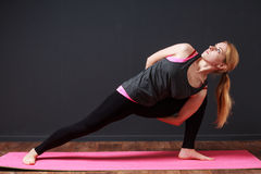 . Young blonde woman doing yoga exercise Royalty Free Stock Photography