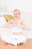 Young blonde woman doing yoga in the living room Stock Images