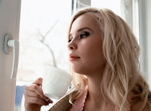 Young blonde woman is dreaming about something while sitting on the window-sill. she holding a tea cup and drinking Stock Image