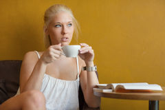 Young blonde woman drinking coffee at cafe Stock Photos