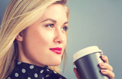 Young blonde woman drinking coffee Stock Image