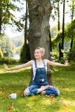 Young blonde woman drinking coffee or tea in the forest sitting in lotus pose and enjoying the warm weather in autumn. Stock Photos