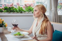 Young blonde woman drinking red wine in an outdoor restaurant royalty free stock images