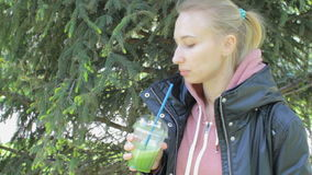 Young blonde woman drinks green vegetable detox smoothie walking in the park stock footage