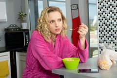 Young blonde woman eating cereals in the morning Royalty Free Stock Image