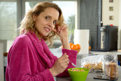 Young blonde woman eating cereals in the morning Royalty Free Stock Images