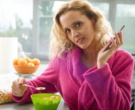 Young blonde woman eating cereals in the morning Stock Photo