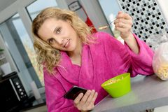 Young blonde woman eating cereals and phone in the morning Stock Photo