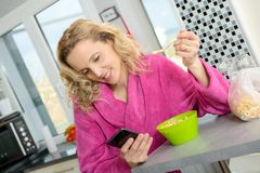 Young blonde woman eating cereals and phone in the morning Stock Photography