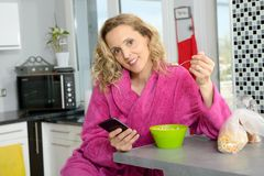 Young blonde woman eating cereals and phone in the morning Royalty Free Stock Images