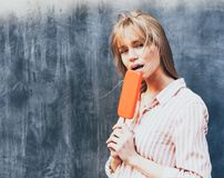 Young blonde woman eating an ice cream. Eskimo. Close-up. stock photos