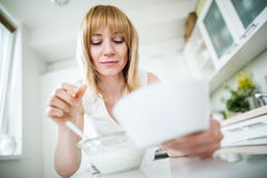 Young blonde woman eating muesli in kitchen Stock Photos