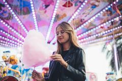 Young blonde woman eats cotton candy floss. Adorable cute pretty woman stands in middle of amusement park, in front of ride with bright colours positive and Stock Photos