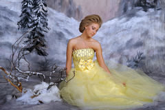 Young blonde woman in an elegant yellow dress Stock Photos
