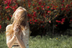 Young blonde woman enjoying aroma blooming garden in the air. Her eyes are closed by hair from pleasure Royalty Free Stock Photography