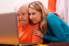 Young blonde woman explains an older an computer. Young female shows an senior how to use modern technology Stock Photos