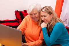 Young blonde woman explains an older an laptop. Young female shows an senior how to use internet Stock Photography