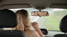 Young blonde woman flossing her teeth in the cab her car. Woman and teeth floss. stock video